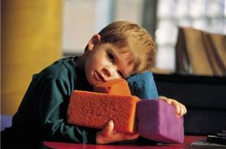 3 or 4 year old boy holding soft, multicolored sponge blocks
