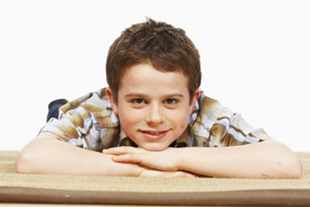 adolescent boy lying on stomach smiling