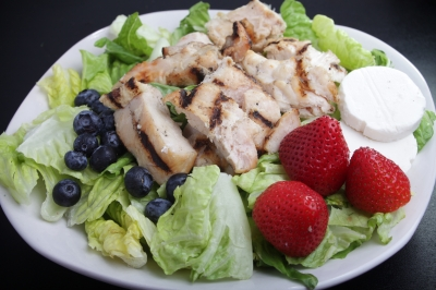 chicken salad on lettuce with blueberries and strawberries, served on a white plate