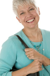 smiling lady with short white hair wearing teal sweater